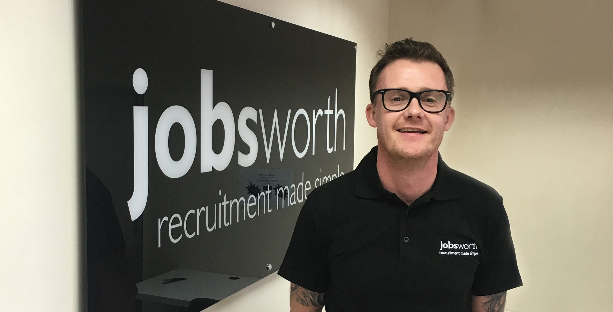 Employee Jay stood infront of Jobsworth sign