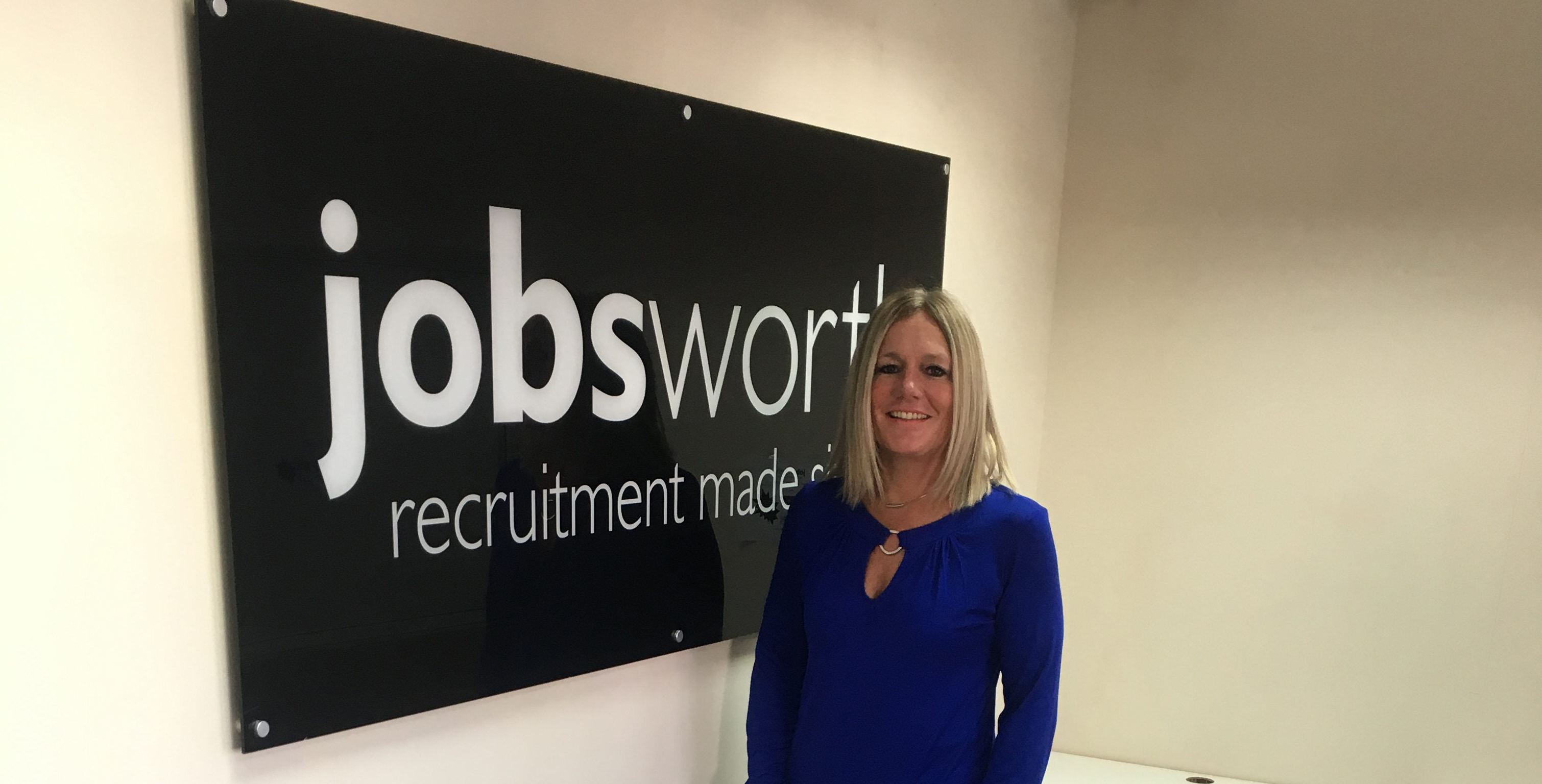 Employee Sarah stood infront of Jobsworth sign