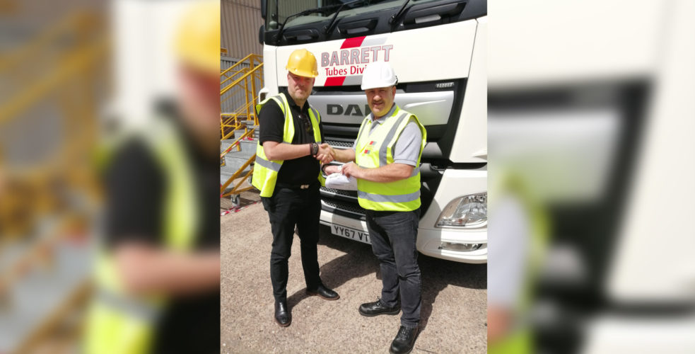 Learner and examiner with certificate shaking hands infront of lorry wearing hard hats and high vis