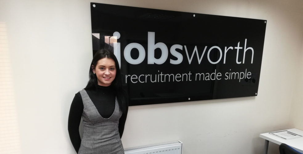 Employee Katie standing infront of Jobsworth sign