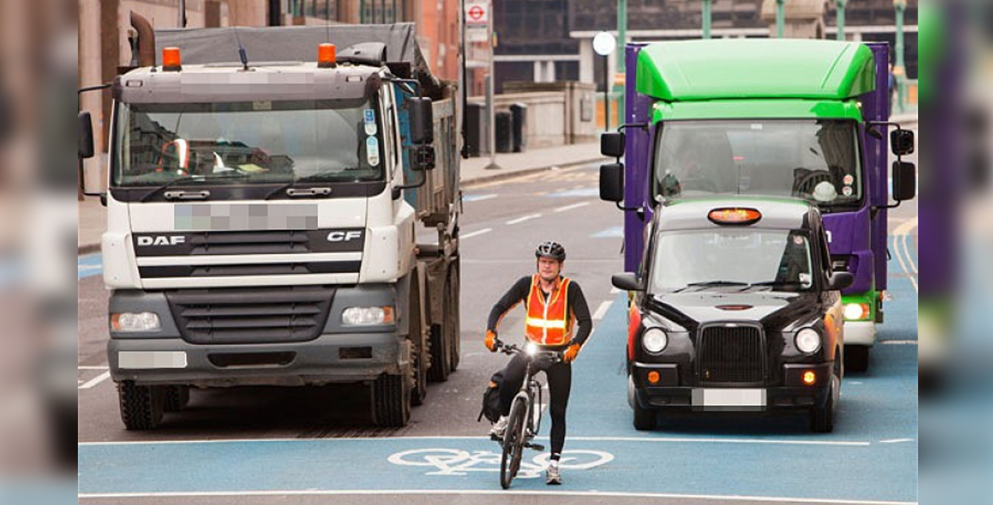 cyclist, taxi and lorries waiting at traffic lights