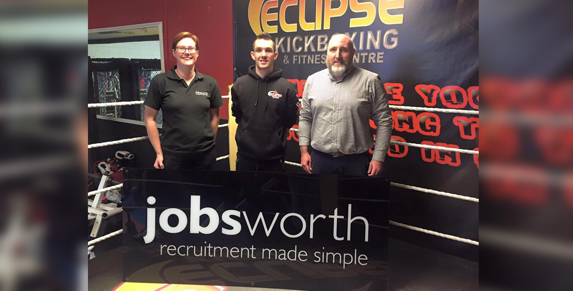 Lucy and Robin with Jobsworth sign stood inside boxing ring with Kyle Williams, local champ