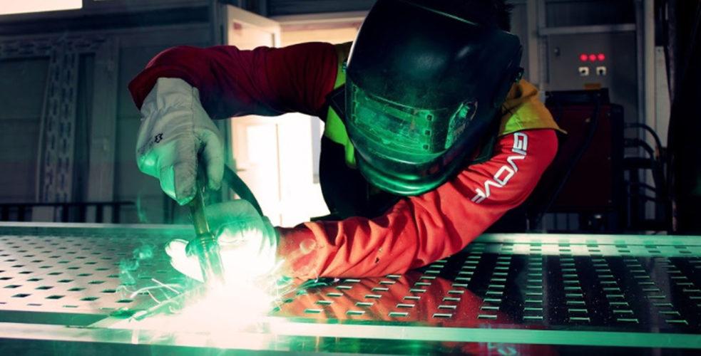 Man welding metal within industrial environment wearing helmet, suit and gloves