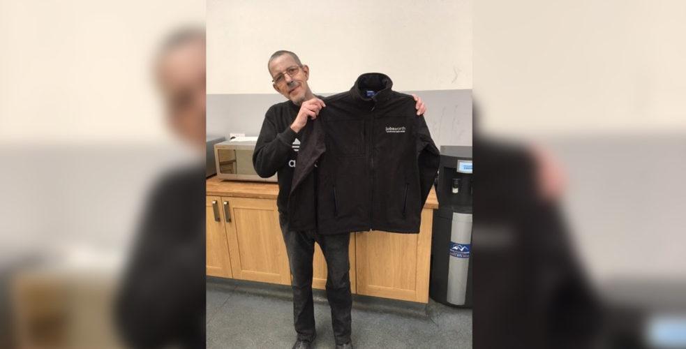Employee holding up Jobsworth branded jacket