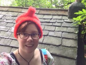 Lucy wearing fuzzy red hat infront of slate roofing