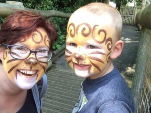 Lucy and her toddler smiling with their face painted as lions